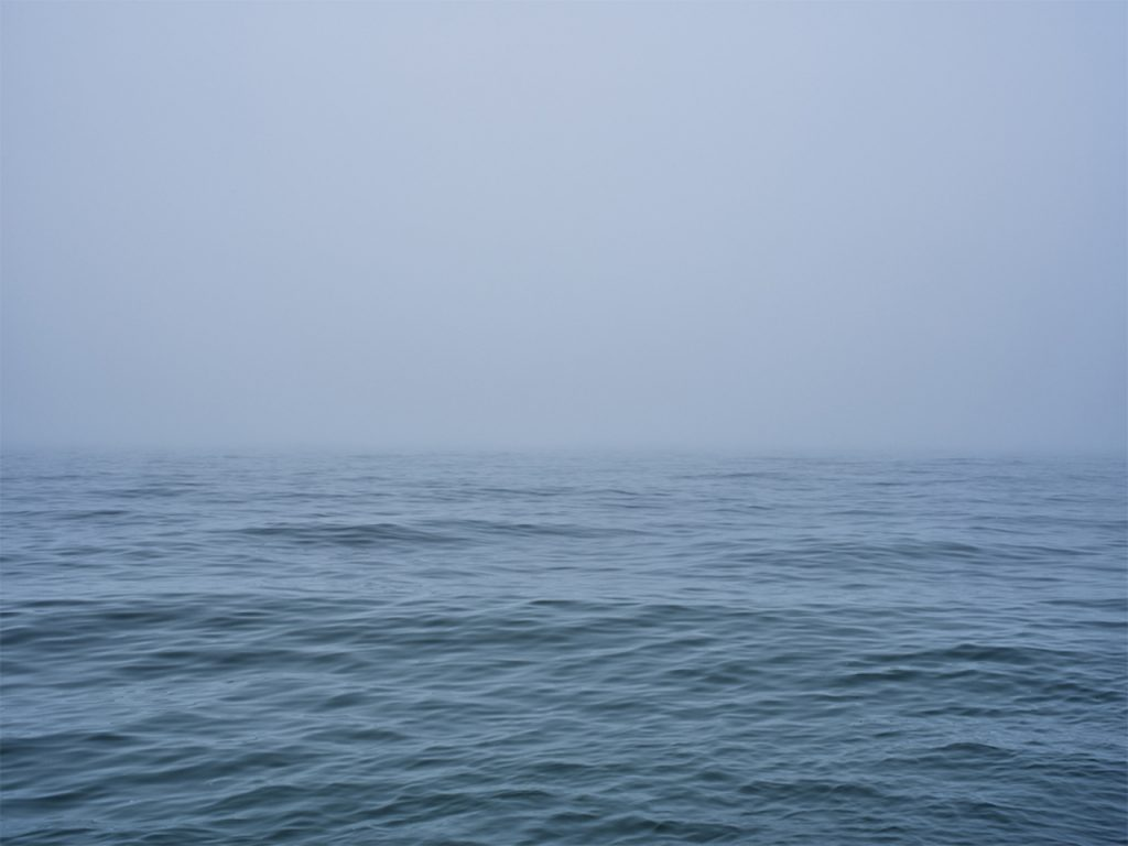 a foggy Lake Michigan early in the morning obscures the view of the horizon