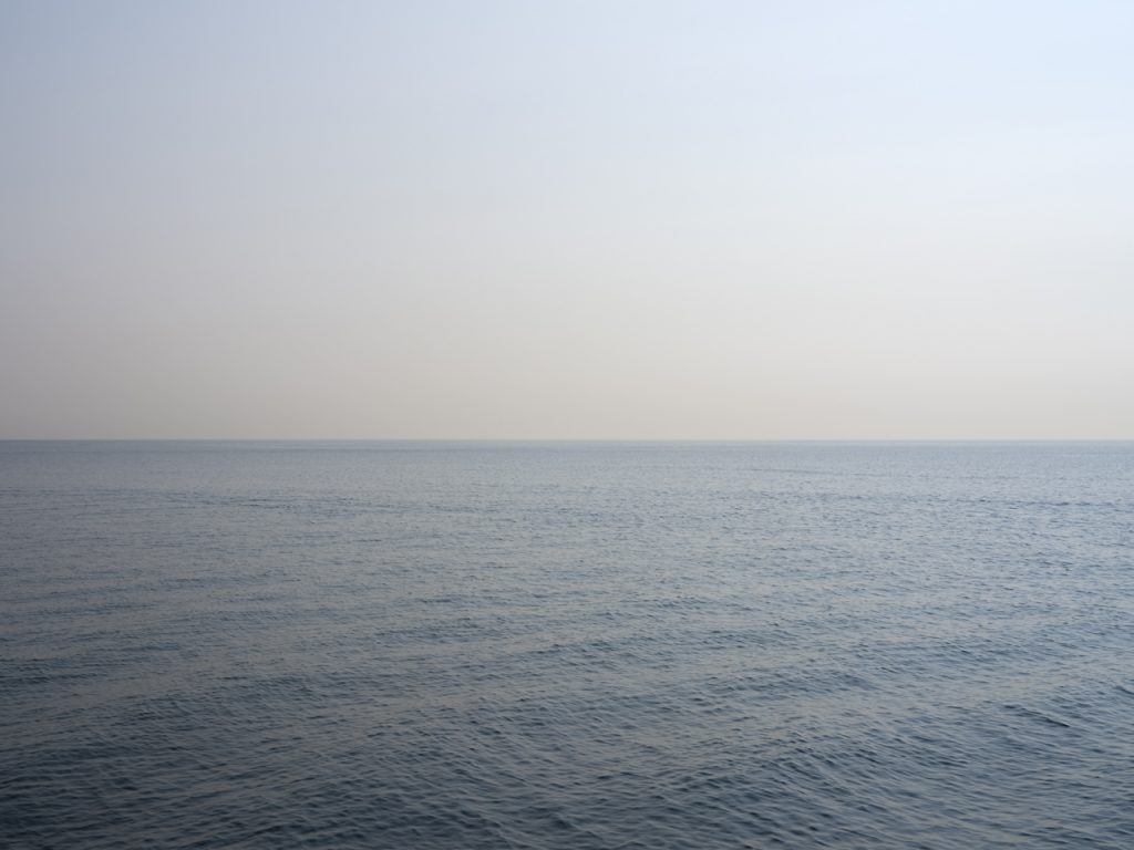 late summer on the lake and the sky is hazy and almost taupe in color, the waters rippling and shifting