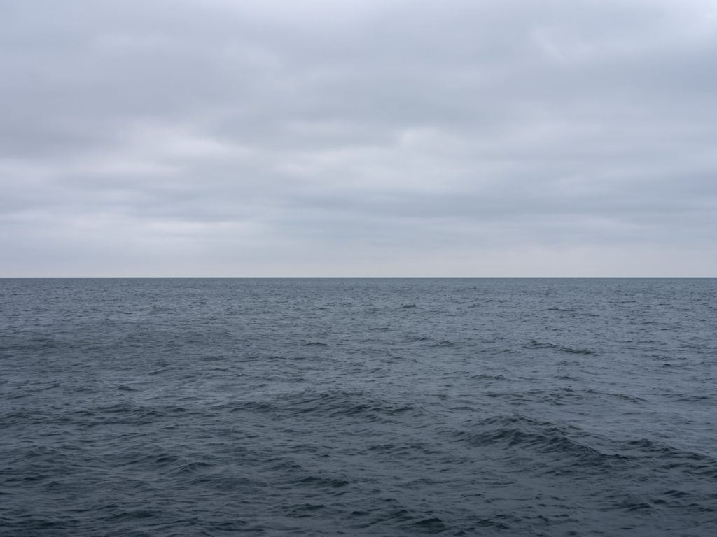 a gray lake dawn on Lake Michigan with heavy clouds over restless lake waters
